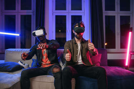 Positive joyful black and caucasian male mates which sitting together on the comfortable couch in cozy stylish livingroom and having competition between each other in video games using virtual reality goggles.