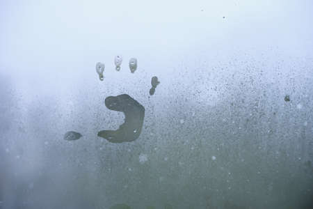 Little child's handprint on foggy glass. Bad weather and depression concept.