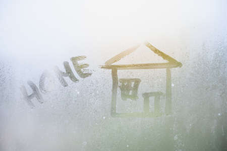 House painted on misted glass. Window glass with raindrops against a rainy cloudy sky. Children's drawings. Standard-Bild