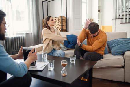 Young fighting angry couple blaming each other for problems, telling its your fault, discussing with psychologist who is right and wrong, misunderstanding and selfishness in marriage. Stock Photo