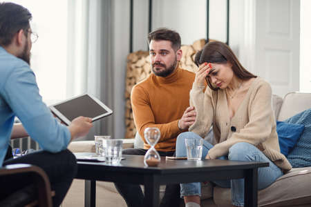 Young fighting angry couple blaming each other for problems, telling its your fault, discussing with psychologist who is right and wrong, misunderstanding and selfishness in marriage. Banque d'images