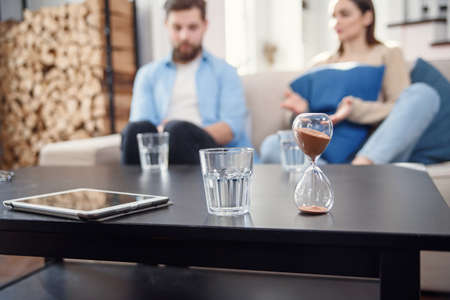 Sand clock at psychologist cabinet with unhappy annoyed caucasian couple having psychologist therapy session on background.