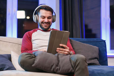 Front view of positive friendly joyful 30-aged guy with well-maintained beard which enjoying cool songs in his headphones and doing dancing movements with hands