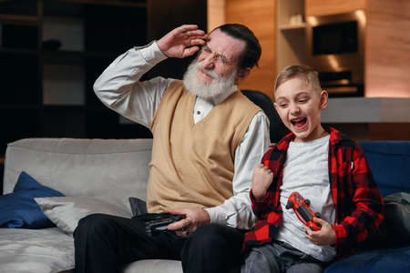 Cute little boy with grandfather sitting on sofa and playing video game with game pad