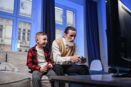 Grandfather and grandson are playing exciting video games on computer with gamepads at home. 스톡 콘텐츠