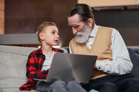Grandson is teaching his grandfather to use laptop computer.