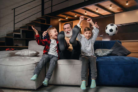 Likable concentrated senior bearded grandfather with his cheerful 10-15s grandsons spending their free time at revision the basketball game on tv Standard-Bild