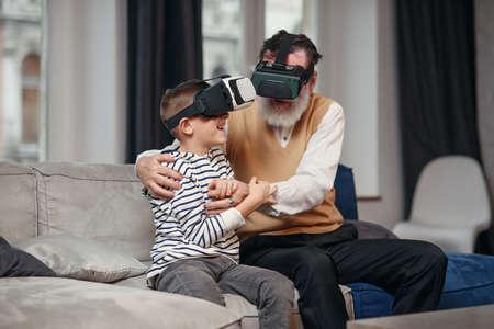 Excited modern senior man with grandson testing VR glasses sitting on comfortable sofa at home. Standard-Bild