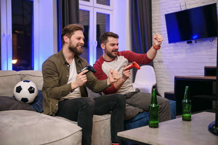 Slow motion of emotional excited funny young multiethnic guys which fooling with each other while playing video games at home ,one bearded guy celebrating victory,second getting lose Banco de Imagens