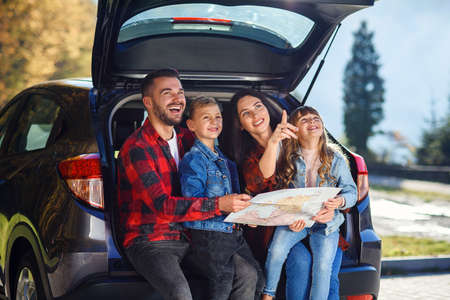 Satisfied family of handsome father, pretty mother and lovely kids which are looking on the road map while sitting in the cars trunk at joint family vacation. Stock fotó