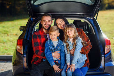 Appealing young modern mother and father and their smiling teen kids which sitting together in the black cars trunk and looking at camera Stock fotó