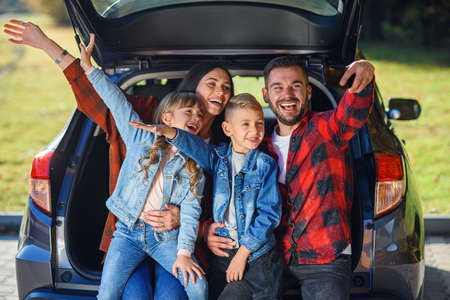 Happy stylish parents with their cute lovely children are making funny selfie on smart phone while sitting in the trunk. Happy modern family concept.