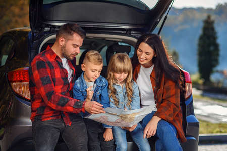 Close up of joyful pleasant family which gethering on their vacation with teen children and using road map to choose the right path on the car