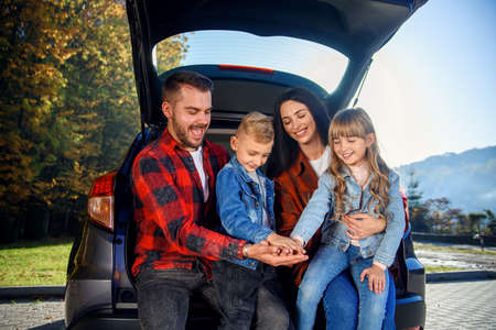 Adorable parents with their lovely kids sitting in the trunk of their family car, laughing and giving five to each other. Enjoying happy family time concept.