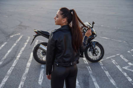 girl with long hair in a leather jacket in an underground parking lot on a motorcycle Imagens
