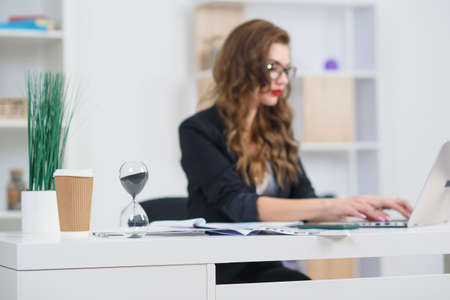 Close up photo of hourglass standing at desk and beautiful business woman working at office.. Stock fotó