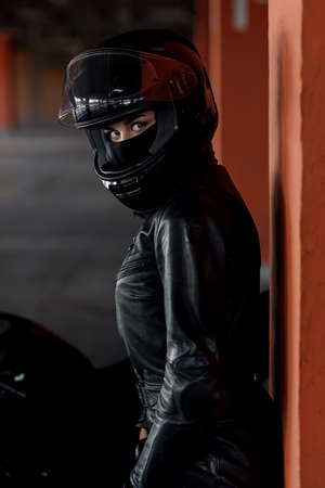 Stylish young woman motorcycle rider with beautiful eyes in black protective gear and full-face helmet near her bike on underground parking. Extremal and freedom concept. Banque d'images