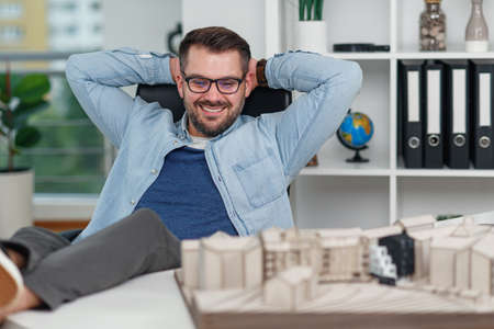 Happy office worker in casual clothes laid his feet on workspace table while dreaming about rest or vacations. Joyful architect relax on the workplace successfully completing his project.