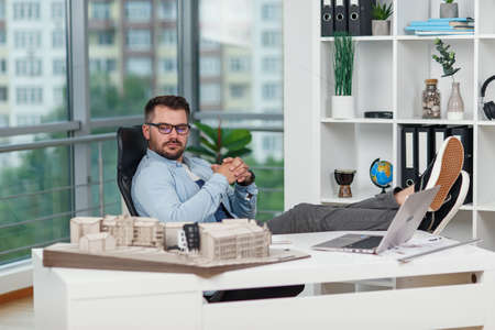 Happy office male worker in casual clothes laid his feet on workspace table while dreaming about rest or vacations. Joyful architect relax on the workplace successfully completing his project.
