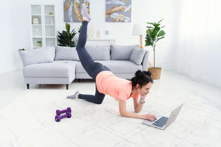 Young sports woman doing workout on the floor at home and watching fitness videos in a laptop. Mom exercising while daughter watching cartoons on background.