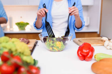 Close up photo of young womans hands mixing fresh vegetables salad in a glass plate at the kitchen.