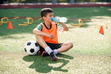 Tired teen boy in soccer uniform drinks with water from plastic bottle after intensive training at stadium in morning. Imagens