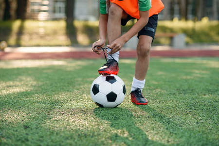 Close up boot of football player which puts his leg on ball and tying shoelace on soccer stadium on the training.