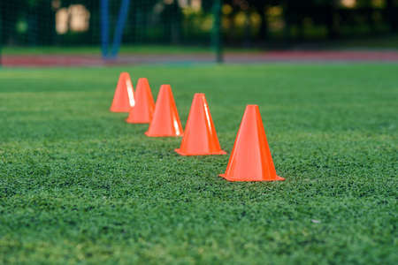 Five orange training cones on an artificial football or soccer green field, Training sports equipment. Stockfoto