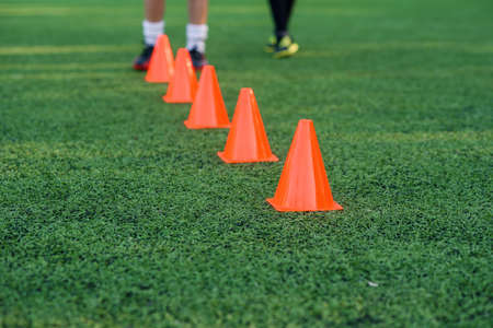 Five orange training cones on an artificial football or soccer green field, Training sports equipment.