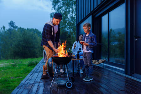 Happy father and son preparing a barbecue on a family vacation on the terrace of their modern house in the evening.
