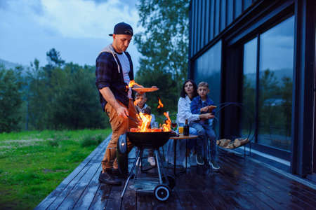 Happy father preparing a barbecue on a family vacation on the terrace of their modern house in the evening.