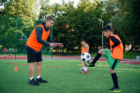 Skillful teen player in football uniform working out the kicking ball together with his experienced coach on sport field