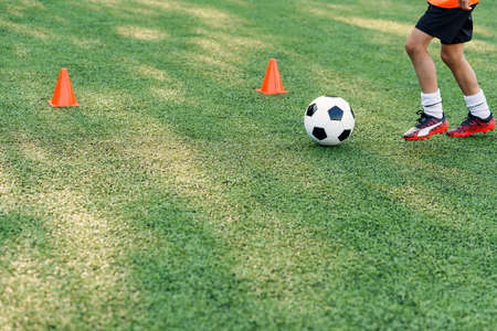 Soccer player kicking ball on field. Soccer players on training session. Close up footballer feet kicking ball on grass.