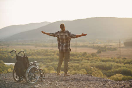 A young man got up to his legs from a wheelchair on top of a mountain at sunrise. The invalid was healed. Imagens