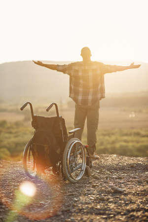 The concept of healed disabled people. A young man got up to his legs from a wheelchair on top of a mountain at sunrise.