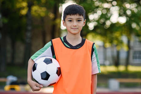 Confident teen football player in orange vest holds a ball in hand after training on outdoors sports field at morning.