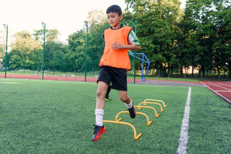 Motivated teen soccer players perform run exercises with overcoming obstacles applying racks on artificial soccer field.