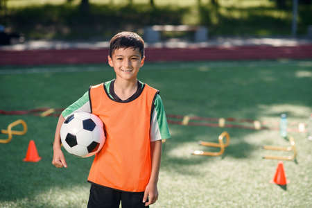 Cute asian boy in soccer uniform with ball after productive training on artificial football stadium on summer day.