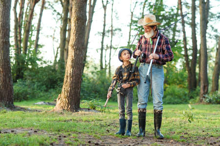 Handsome bearded grandfather spending leisure with his grandson going fishing. Family and hobby time concept. 免版税图像 - 156063534