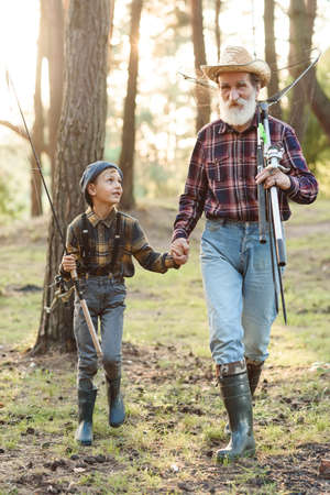 Handsome bearded grandfather spending leisure with his grandson going fishing. Family and hobby time concept.