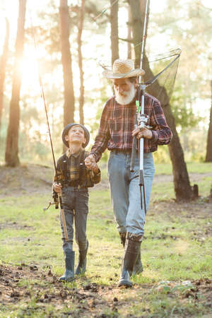 Likable confident bearded grandpa in forest going fishing together with his 10-aged grandson and talking about fishing. 免版税图像