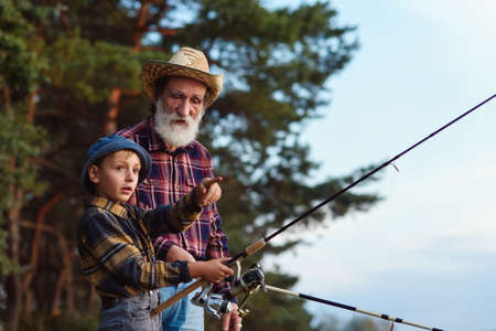 Stylish experienced bearded grandpa in straw hat fishing together with his curious grandchild on the lake at sunset.
