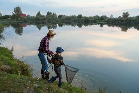 Cute 10-aged boy with his experienced grey-bearded 70-aged grandpa catching fish on the lake with landing net at sunset