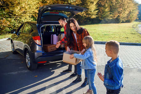 High-spirited likable parents unloading the autos trunk with their cute 10-12s kids during moving into new apartment.