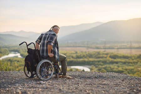 A young man getting up from a wheelchair on top of a mountain at sunrise. The invalid was healed.