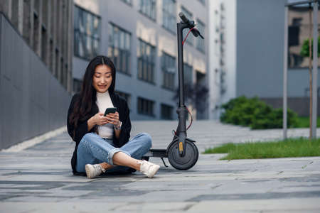 Smiling confident 25-aged asian girl resting on asphalt near electric scooter and browsing social media at smartphone. 스톡 콘텐츠
