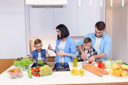 Happy caucasian family with two sons preparing healthy vegetarian breakfast with and vegetables on cozy kitchen.