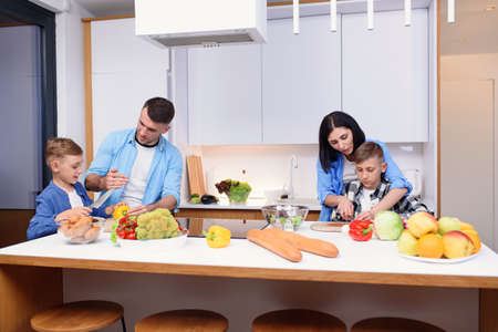 Stylish young family with two sons preparing healthy vegetarian breakfast with fresh vegetables on cozy home kitchen.
