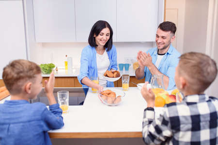 Joyful family of four persons drink orange juice with croissants and tasty cakes in the kitchen. Happy family concept. 免版税图像