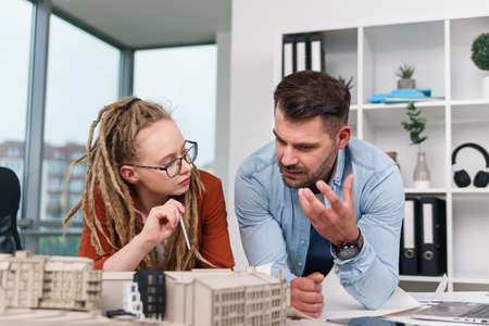 A male architect and a female designer are discussing a joint project for a future residential complex. Stock Photo